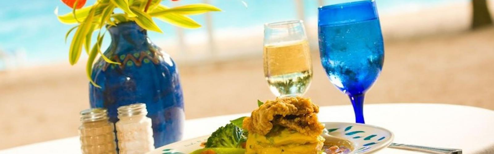 blue glass and blue vase on table at beach with fish