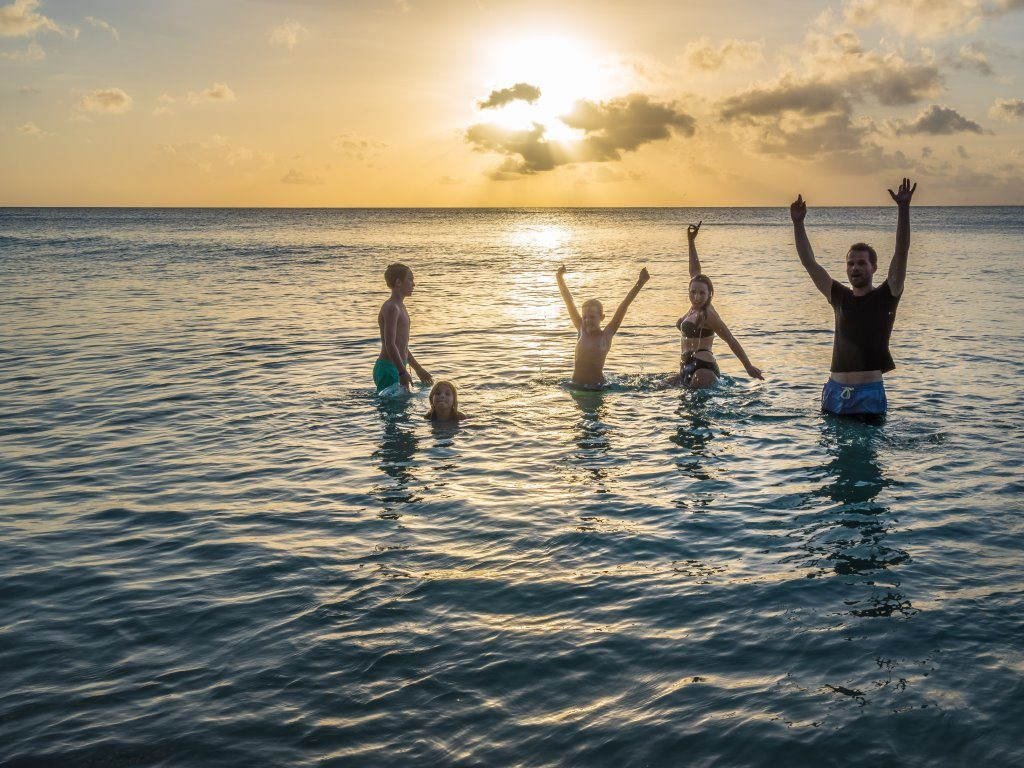 Happy Family with arms in the air in the sea as sun sets on an eco holiday